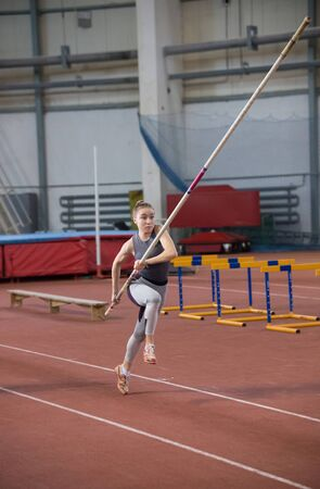 Pole vaulting - young woman is scattering with pole in hands
