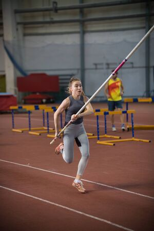 Pole vaulting - woman is running with a long pole in her hands