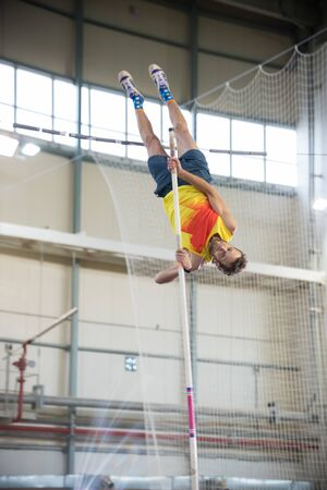 Pole vaulting - man with beard is reaching the bar on the pole