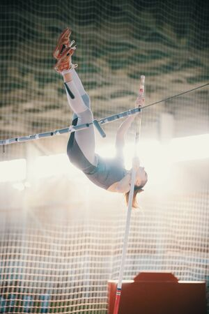 Pole vaulting - woman with ponytail is jumping over the bar