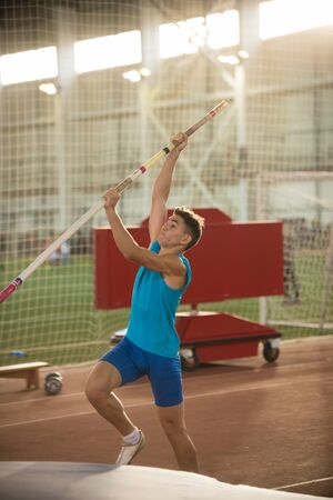 Pole vaulting - man in blue shirt is going to jump with pole Stockfoto