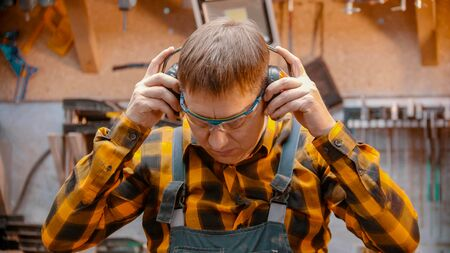 Carpentry indoors - a man woodworker put on a protective soundproof headphones Фото со стока