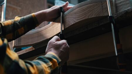 Carpentry works - a man woodworker measuring the detail width