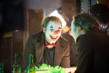 Clown concept - a crazy man clown looking at his mirror reflection in the dressing room and laughing