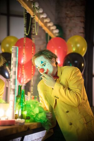 Clown concept - a lost man clown in yellow jacket lighting up a cigarette in the dressing room