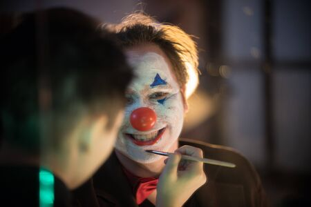 Clown concept - Make-up artist applying paint on the man clown in the dressing room Stock fotó