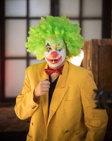 Clown concept - a lost man clown in yellow jacket and green wig with a cigarette in his mouth Stock fotó