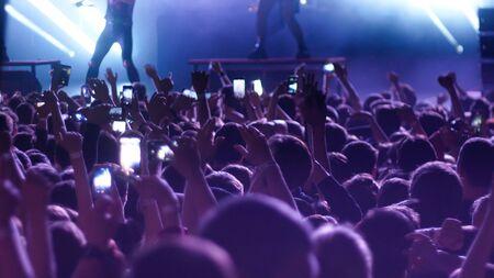 コンサートで手を上げて踊るエネルギッシュな人々。ミッドショット