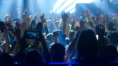Energetic people dancing with their hands up at the rock concert - blue lighting. Mid shot Banque d'images