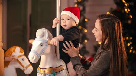 Weihnachtsdekoriertes Studio - Eine lächelnde junge Mutter, die in der Nähe ihres Babys auf dem Karussell steht