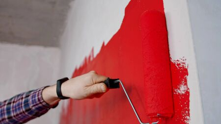 Covering wall in red paint in new apartment. Mid shot