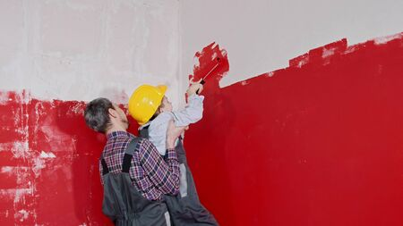 A little boy and his father painting walls - father helps his son to paint upper wall. Mid shot 스톡 콘텐츠
