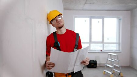 A tired man worker holding apartment plan and thinking about it. Mid shot