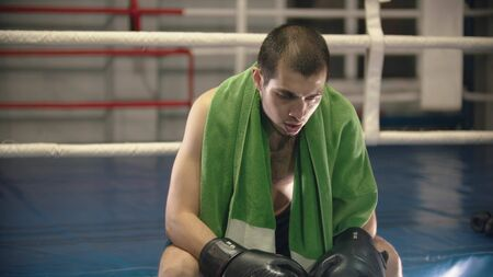A tired man boxer sitting on the ring with green towel on his shoulders
