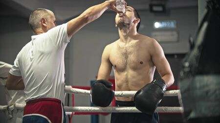 A trainer pours water in the boxers mouth on the ring. Mid shot