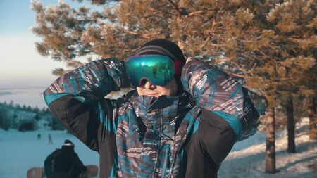 A man snowboarder putting on protective glasses
