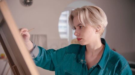 A young blonde attractive woman artist draws a painting