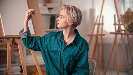 A young woman artist looking at the golden paint tube