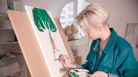 A young blonde woman draws a tree using colorful paints