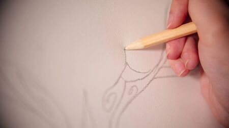 A young woman sketching with a pencil on the canvas 写真素材
