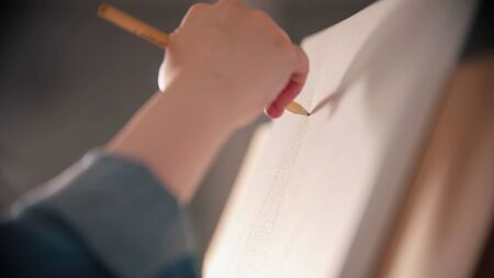 A young woman sketching on the canvas using pencil 写真素材