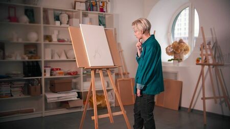 A young woman sketching an abstract tree on the canvas and looking at it