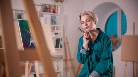 A young woman artist sitting in the art studio after finishing the painting