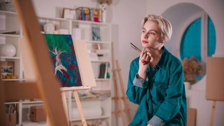 A young woman artist sitting in the art studio after finishing the painting holding brushes 写真素材