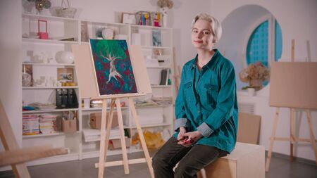 A young woman artist with short blonde hair sitting in the art studio