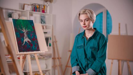 A young woman artist with short hair sitting in the art studio