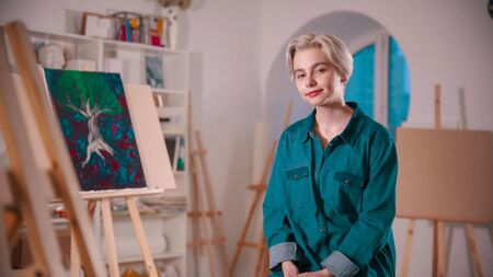 A young smiling woman artist with short blonde hair sitting in the art studio 写真素材