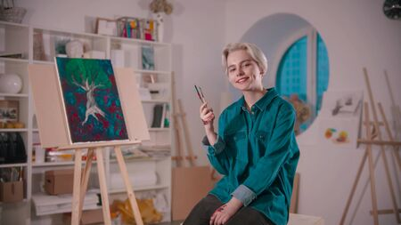A young smiling woman artist sitting in the art studio after finishing the painting holding brushes