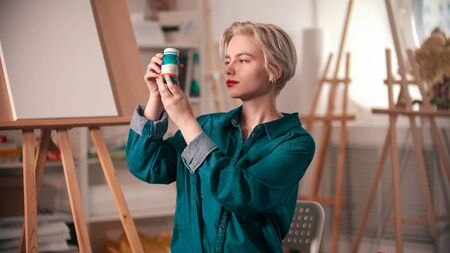 A young woman artist opening up a blue paint tube 写真素材