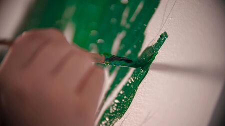 A young womans hand painting a green crown of the tree on the canvas. Mid shot