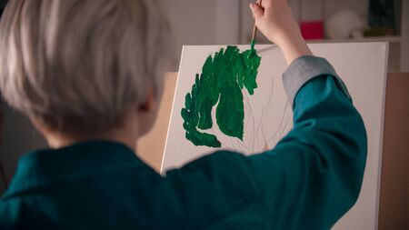 A young blonde woman coloring a tree crown on her painting. Mid shot