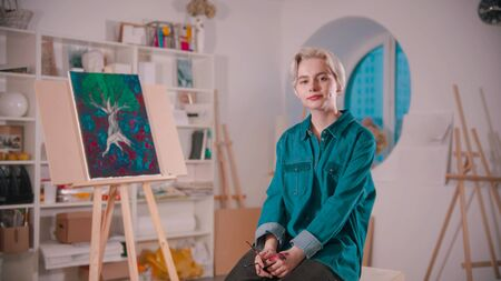 A young woman artist with short blonde hair sitting in the art studio - her painting on the background