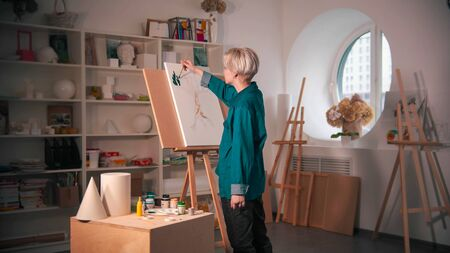 A young woman artist painting upper branches of tree in green color in the art studio. Mid shot