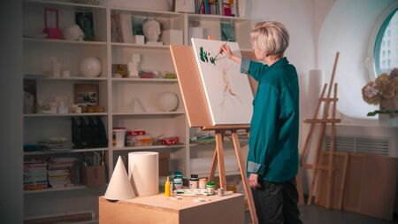 A young woman artist with short hair painting upper branches of tree in green color in the art studio. Mid shot