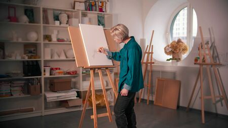 A young woman sketching tree on the canvas. Mid shot