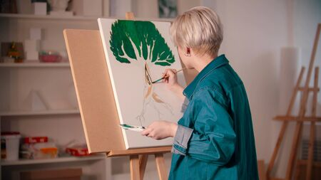 A young woman artist coloring her painting in the art studio. Mid shot