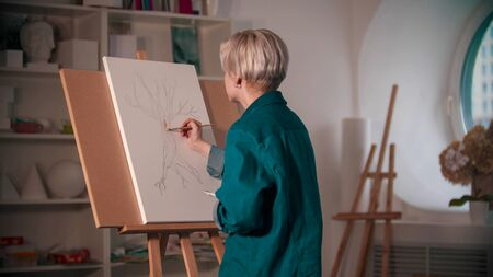 A young woman artist coloring her painting of the tree. Mid shot