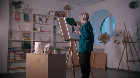 A young woman artist in the art studio - making a tree painting - a skull and other figures on the table. Mid shot