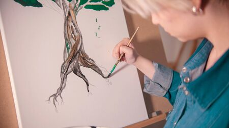 A young woman painting tree trunk in darker color