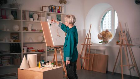 A young woman artist coloring her painting. Mid shot