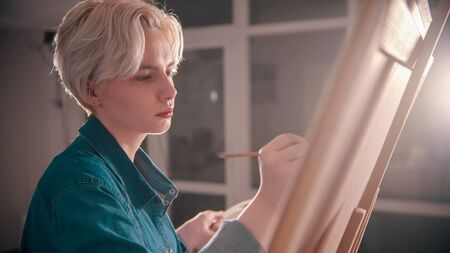 A young blonde attractive woman artist draws a painting in the art studio 写真素材