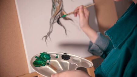 A young woman artist painting tree trunk in darker color. Mid shot 写真素材