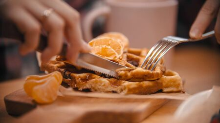 A woman cutting a waffle surrounded by mandarin slices in the plate. Mid shot