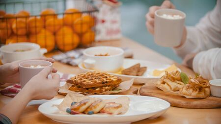 A couple in restaurant having a breakfast of waffles and pancakes. Mid shot