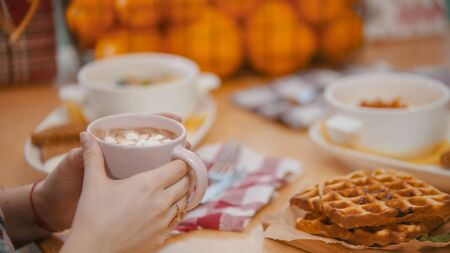 A couple in restaurant having a breakfast of waffles and pancakes - drinking a coffee with marshmallows. Mid shot