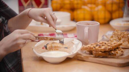 Una donna che taglia una frittella nel piatto. Colpo centrale
